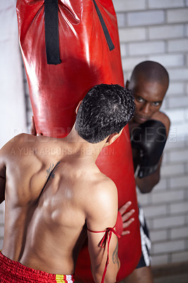 Buy stock photo Two boxers practicing on a punching bag together