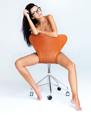 Buy stock photo Portrait of a nude model seated on a chair with her hand in her hair isolated on a white background