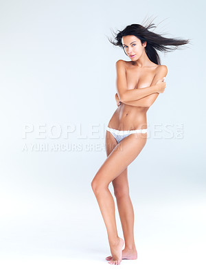 Buy stock photo A full length studio portrait of a beautiful model covering her breasts with her arms and wearing only underwear