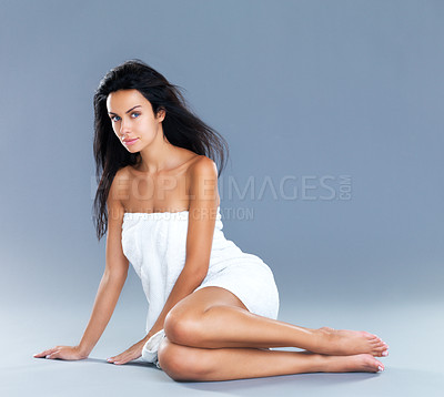Buy stock photo Studio shot of an attractive female model sitting on the floor wrapped in a white bath towel