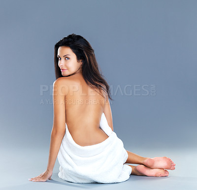 Buy stock photo A rear view shot of an attractive model wrapped in a towel while sitting on the floor and looking back at the camera