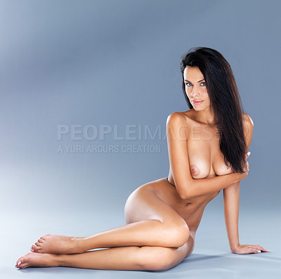 Buy stock photo A studio shot of an attractive naked model lying on the floor leaning on one arm
