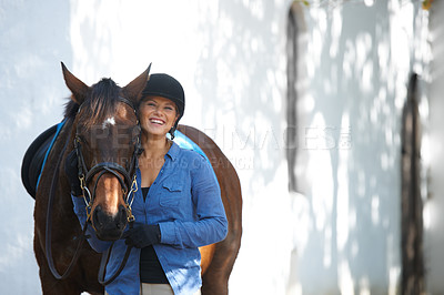 Buy stock photo A happy young woman standing outside with her horse