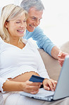 Smiling pregnant woman with her husband shopping online