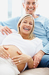 Mature pregnant woman with her loving husband relaxing at home