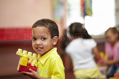 Buy stock photo Portrait of a small boy holding some plastic blocks in a preschool class
