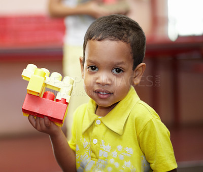 Buy stock photo Portrait of an ethnic boy holding up some plastic blocks in his preschool class