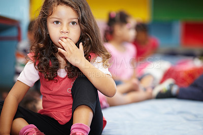 Buy stock photo Beautiful little girl putting her hand in her mouth and looking off in the distance in her preschool class with copyspace.