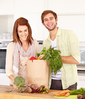 Buy stock photo A happy couple unpacking their grocery bag in the kitchen