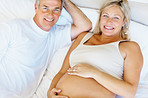 Happy mature pregnant couple lying in bed
