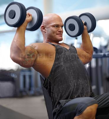 Buy stock photo Shot of a male bodybuilder lifting weights at the gym