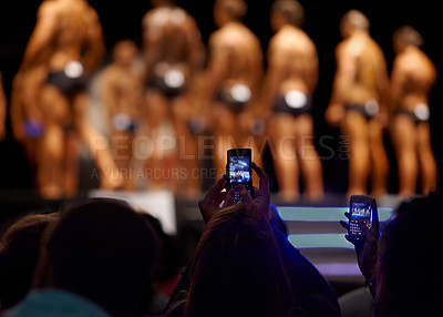 Buy stock photo The audience of a bodybuilding competition taking photographs of the contestants with their cellphones
