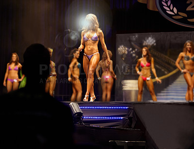Buy stock photo A female bodybuilding contestant walking the stage for the judges