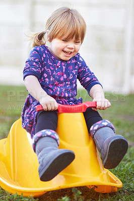 Buy stock photo A cute baby girl sitting on a rocker  outside