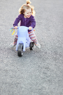 Buy stock photo A cute baby girl riding her tricycle outside on the street
