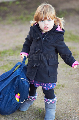 Buy stock photo Portrait of a cute baby girl wearing a jacket and holding a backpack