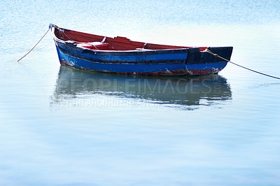 Buy stock photo Shot of an empty fishing boat floating on calm waters