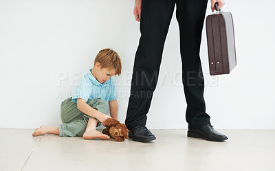 Buy stock photo A young boy holding a teddybear and looking sad because his dad has to go to work