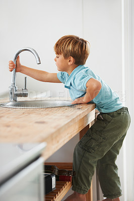 Buy stock photo A cute young boy climbing the kitchen counter to get to the tap