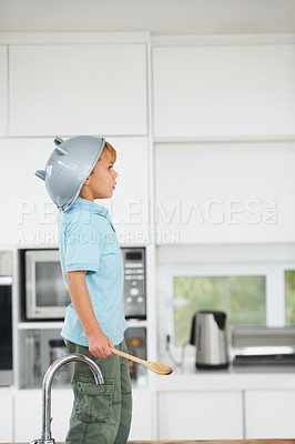 Buy stock photo A cute young boy using a rice strainer as a helmet and a wooden spoon as a sword in the kitchen