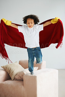 Buy stock photo A cute young boy jumping off his lounge sofa holding a blanket like a superhero's cape