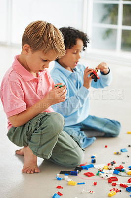 Buy stock photo Two cute young boys playing with building blocks on the flor