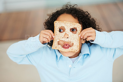 Buy stock photo Shot of a little boy holding up a slice of bread with a cut out smiley face