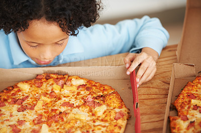 Buy stock photo A cute young boy looking at the pizza in front of him