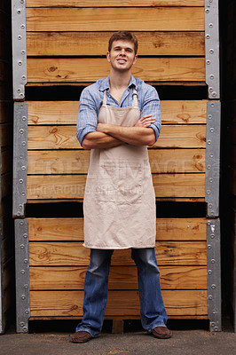 Buy stock photo Portrait of a young wine maker standing in front of wooden crates