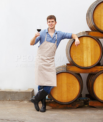 Buy stock photo A young wine maker holding a glass of red wine while leaning on a barrel
