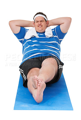 Buy stock photo An obese young man straining to complete a sit up