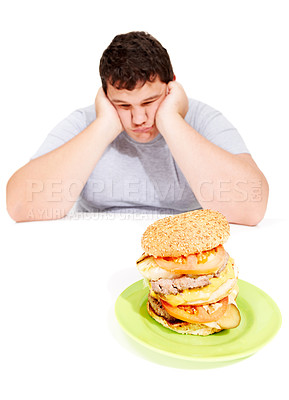 Buy stock photo A dejecting young obese man holds his head in his hands while looking at a huge burger