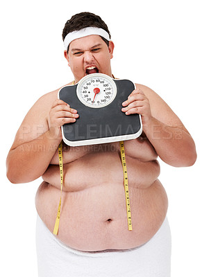 Buy stock photo An obese young man taking his frustration out on a weight scale