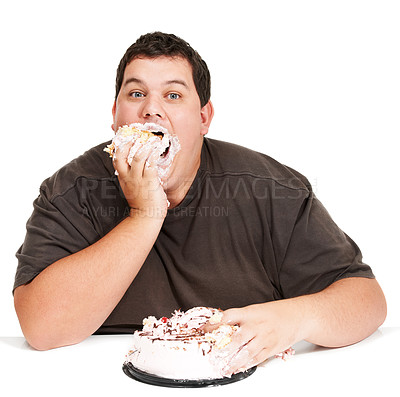 Buy stock photo An obese young man stuffing a cake down his face and not being too dainty about it