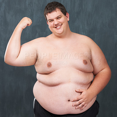 Buy stock photo Studio shot of an obese young shirtless man flexing his bicep