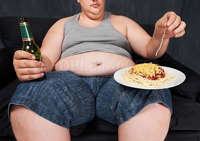Buy stock photo A cropped shot of an obese young man sitting on a sofa and eating spaghetti with his hands