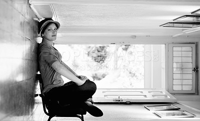 Buy stock photo A woman sitting on a chair inside her house with the house turned sideways - perspective
