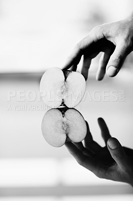 Buy stock photo A hand holding half an apple against a shiny surface  with it's reflection underneath