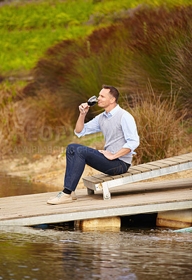 Buy stock photo Portrait of a mature wine maker sitting on a jetty with a glass of red wine