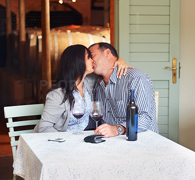 Buy stock photo A happy mature couple kissing while having a bottle of wine in a wine cellar