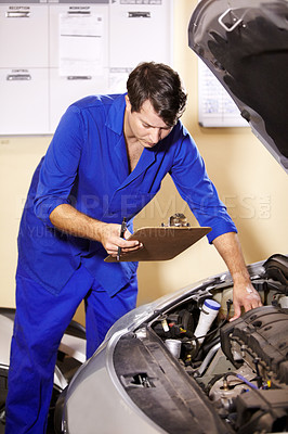 Buy stock photo A male mechanic holding a clipboard while working on the engine of a car