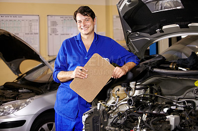 Buy stock photo Portrait of a male mechanic holding a clipboard while working on a car