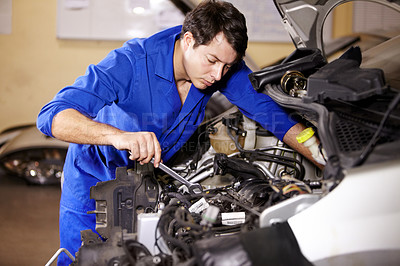 Buy stock photo A male mechanic working with a spanner on an engine of a car