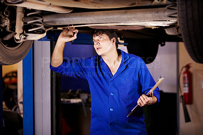 Buy stock photo A young male mechanic looking at the steering rack under a car while holding a clipboard and pen