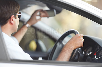 Buy stock photo A man adjusting his rear view mirror while driving