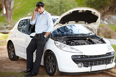 Buy stock photo A man calling roadside assistance on his cellphone because his car has broken down