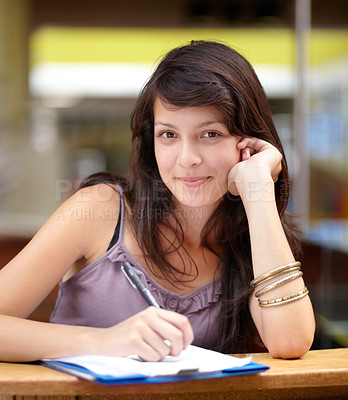 Buy stock photo A young attractive Indian woman taking notes in class
