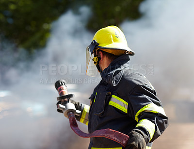 Buy stock photo A caucasian fireman holding a hose and surrounded by the smoke from the fire he's just extinguished