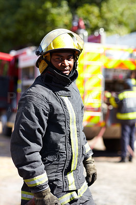 Buy stock photo Portrait of an african fireman standing with his team in the background