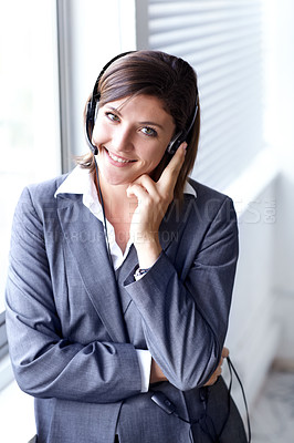 Buy stock photo Portrait of an attractive telemarketer standing in the office with a headset